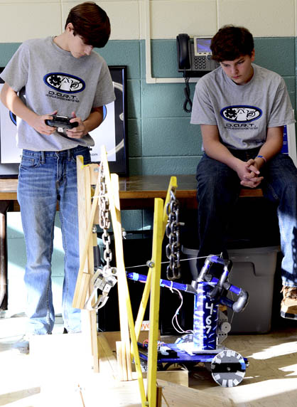 Chance McVay, left, and Jake Jacobs guide D.A.R.T.'s robot through the course.