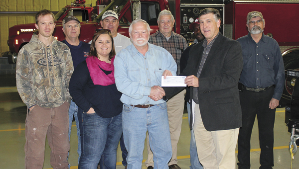 Jefferson VFD members accept a check for $5,000 from the GP Bucket Brigade. Pictured, left to right, are Tom Whitaker, Tim Day, Betsy Compton, O'Neal Parker, George Norris, Joe Coats, Bobby Lynch, GP Mill Manager Ronnie Hall, and Lewis Compton.