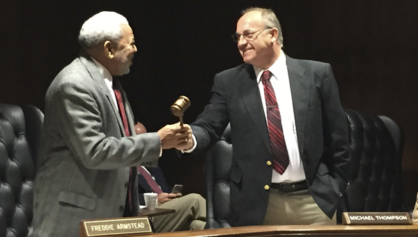 Commissioner Michael Thompson passes the gavel to Commissioner Freddie Thompson during Tuesday's regular meeting.