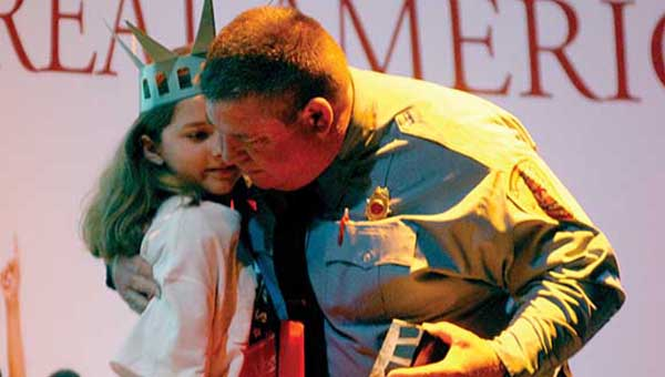 U.S. Jones Elementary School fifth grader Mary Foster presents her father, Demopolis firefighter Chris Foster, with a Statue of Liberty replica during the ceremony to honor local heroes. (Times Staff/Andy Brown)