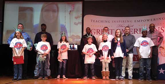 Each of the seventh fifth-grade classes at U.S. Jones Elementary School selected a community hero to recognize during the Super Citizen Program graduation ceremony on Tuesday. Pictured are, back row from left to right, Chris Foster, Ralph Mullens, Sydney Hasty (on the screen), Patrick Braxton, Valley Harrison, Skibo Holman and Byron Franklin. Front row, from left to right, Mary Foster, Houston Jones, Sarah Jordan, John Alex Courtney, Molly Harrison, Mary Grace Smith and Brandon Franklin. (Times Staff/Andy Brown)