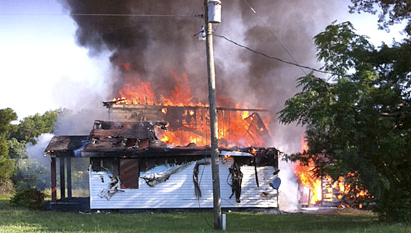 Witnesses said they saw sparks from a power line at the back corner of this house about the time it caught fire on Sunday, July 26.