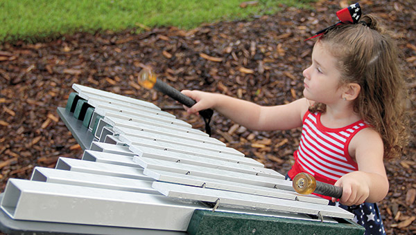 Ryleigh Samples, 2, of Demopolis plays musical instruments that were recently installed at city landing playground.