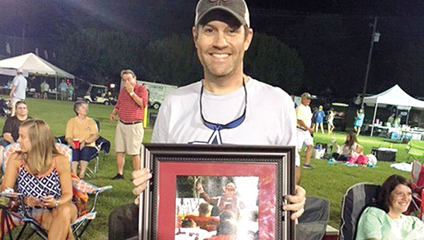 Dan Harper was presented with a photograph of Nick Saban during a fundraising event held in his honor. Harper was recently diagnosed with colon cancer.