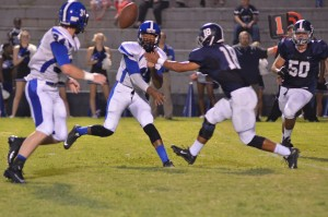 Demopolis quarterback Jamarcus Ezell pitches the ball to Andrew Jones (No. 34) before he is hit by Jemison defender Roberto Abarca (18) on a play that resulted in a 14-yard touchdown (Photo by Stephen Dawkins).