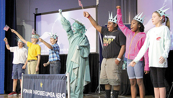 Students wear Statue of Liberty hats and waving American Flags during a kickoff of the Liberty Learning Program at U.S. Jones Elementary School. The program provides civic, character, finance, and career education opportunities.