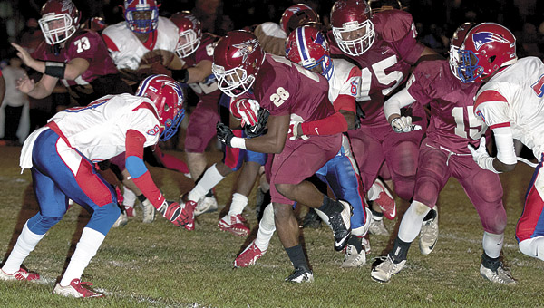 The Patriots' Charles Blackmon (6) and Jaleel Jones (8) attempt to stop Maplesville's Terence Dunlap who ended the semi-state game with 201 rushing yards.