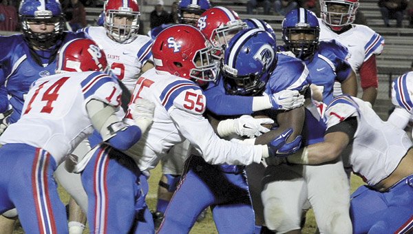 Jay Craig attempts to pick up yardage against the St. Paul's defense in the third round of the 5A state playoffs Friday. The Saints' defense held the powerful Demopolis running game in check most of the night.