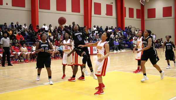 Courtney Hill tries to sink a layup under heavy pressure. Hill finished as one of the leading scorers in this contest.