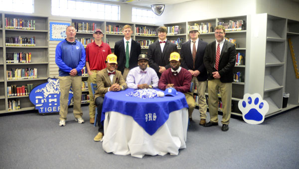 Seven DHS Tigers sign scholarships to play at the collegiate level. They are picture here with Athletic Director Stacy Luker on the far left and DHS Principal Christopher Tangle on the far right.