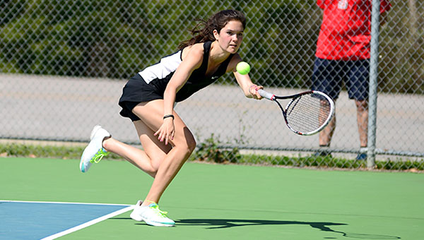 Abigail Hathcock stretches out to keep a rally alive in her singles match against Trinity Presbyterian High School Tuesday during a tennis match on the Demopolis High School campus.