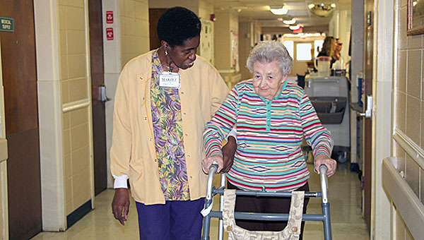 Marzet Besteder assists Woodhaven Manor resident Shirley Burton. Besteder has provided care to residents at Woodhaven for 40 years.