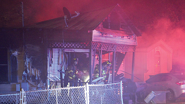 Firefighters work the scene of a house fire on First Avenue in Dempolis early Wednesday. A 19-year-old was killed in the blaze while two adults were able to escape.