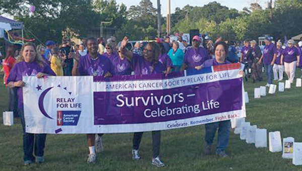 Cancer survivors take to the track lined with memorials for the annual Survivors' Walk that kicks off Relay for Life Night. The event was held Friday, May 6, at the Demopolis City Landing. This year, 12 teams joined together to raise over $30,000 for the American Cancer Society. PHOTO BY MELANIE SORONEN