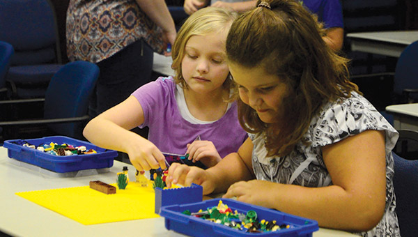Abby Acker and Katie Hardin work together to make a story using LEGO blocks during the LEGO Engineering Camp hosted by Shelton State Community College at the Demopolis Higher Education Center.