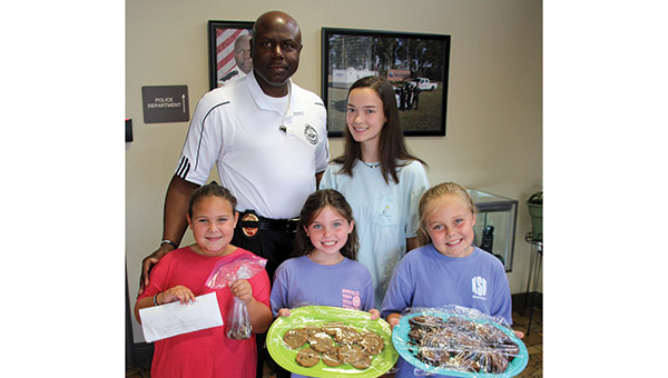 From left, (front) Halle Hynniman, Maddie Grace Tiel and Mary Carlton Parten donates money they raised through a lemonade stand to the Dempolis Police Department to help provide school supplies for other children. Pictured with the girls are DPD Chief Tommie Reese and the girls' sitter, who helped them with the fundraiser, Natalie Saliba.