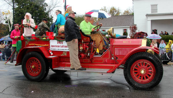Woody Collins drives the old fire truck through town during a rainy COTR in 2016.