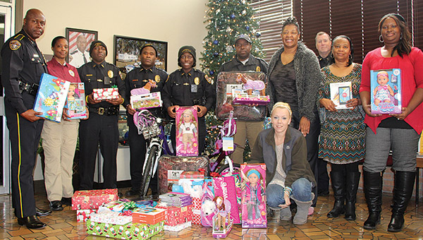 The Demopolis Police Department donated toys and presents to two families for Christmas. Pictured above are DPD representatives along with Crystal Williams (kneeling) with the gifts purchased for her family, which includes three daughters.